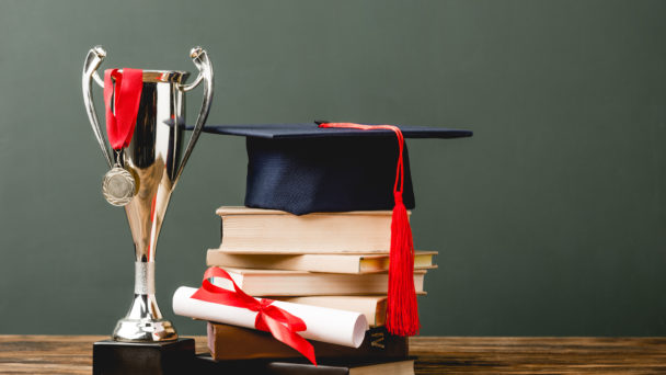 En hög med böcker med en studenthatt på. Bredvid står en prispokal.