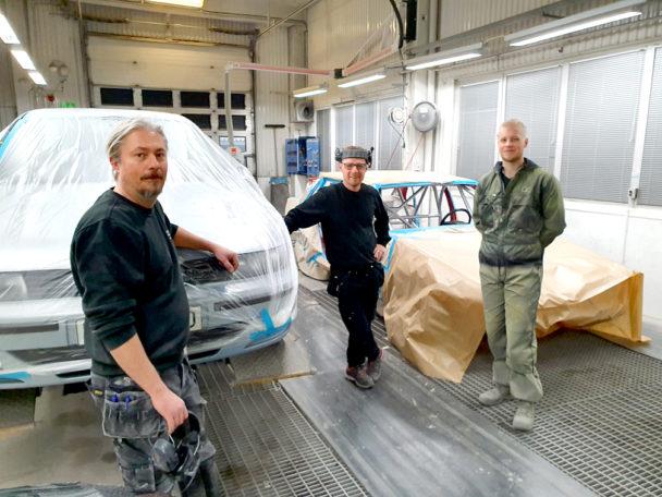 Tre personer står i en verkstad invid en bil.