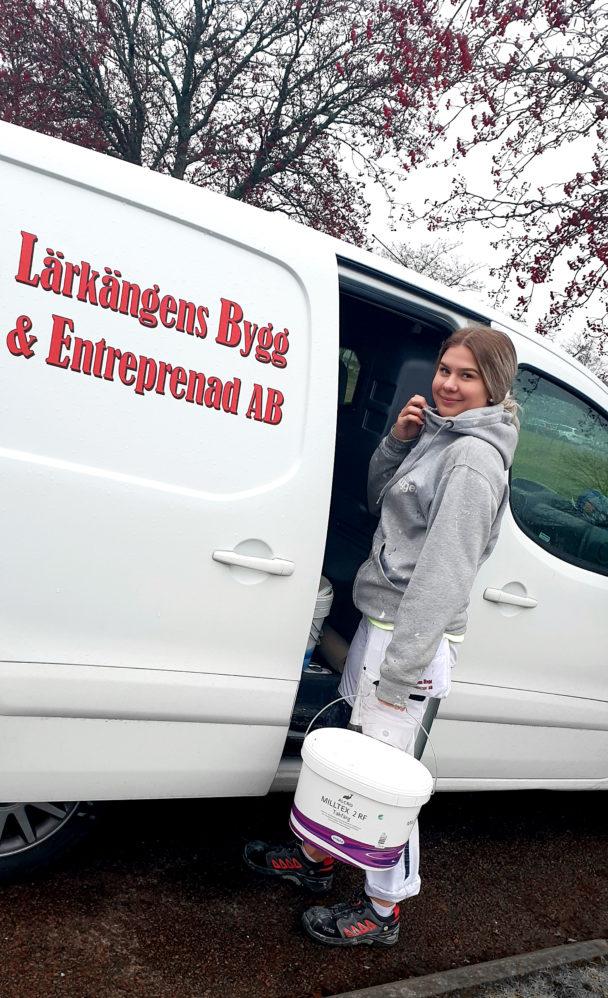 Isabelle Nilsson framför firmabilen.