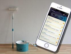 En mobiltelefon med appen på skärmen, framför en roller och en färghink.