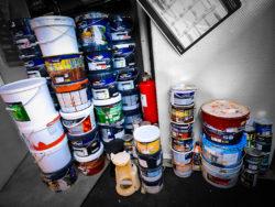 Travar med färgburkar i ett litet rum