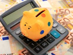 En spargris på en miniräknare som ligger på en bädd av sedlar