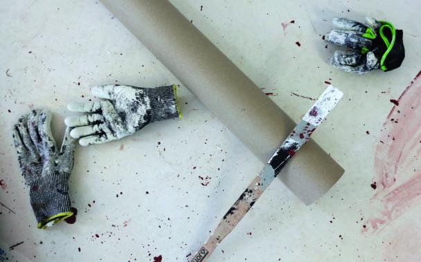 Penslar och handskar täckte med vit färg på ett golv.