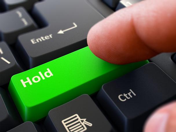 """Ett finger ovanför en grön tangentbordsknapp med ordet """"Hold"""" på"""