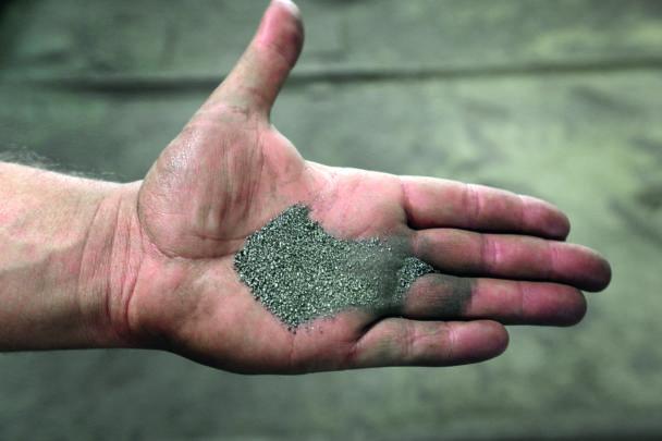 En hand med ett grått pulver i