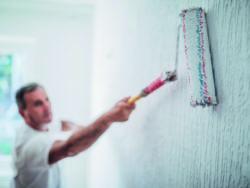 En person målar en vägg med en roller