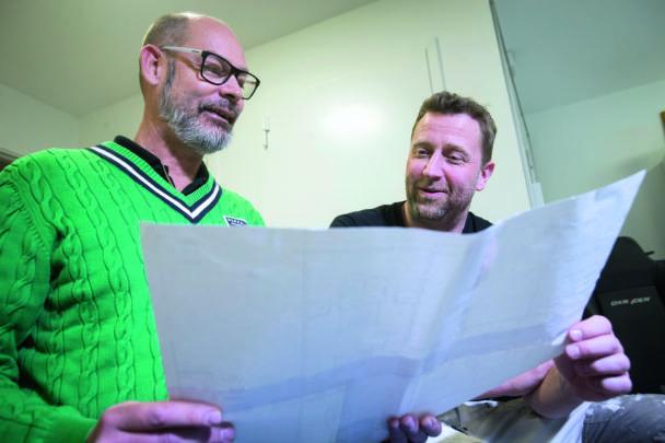 Två personer tittar tillsammans på ett stort papper
