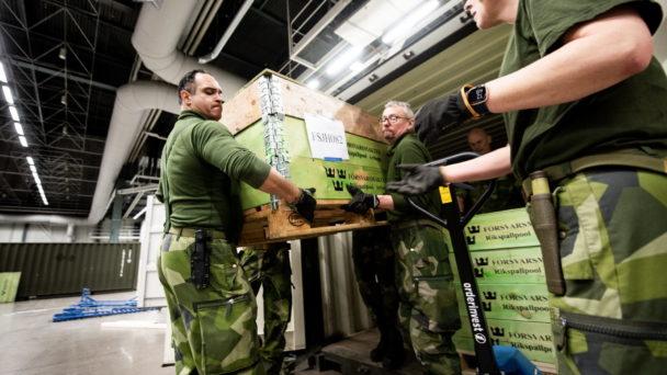 Två personer i kamouflagekläder bär stora lådor