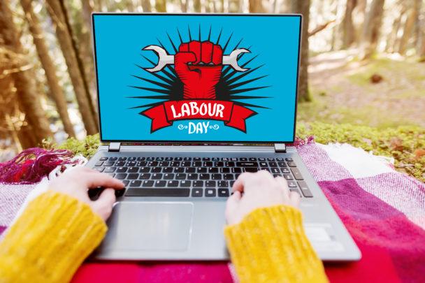 En laptop utomhus, med en tecknad bild på skrärmen av en hand som håller i en skiftnyckel över texten Labour Day