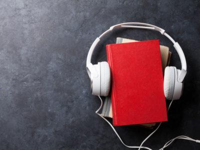 En trave böcker med ett par hörlurar kring sig