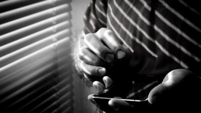 En person står vid ett fönster och tittar på en mobiltelefon
