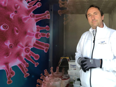 Joakim Winberg på arbetsplatsen monterat invid en närbild på det nya coronaviruset SARS-CoV-2