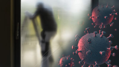 Silhuetten av en målare bakom en skyddsplast, med en bild av det nya coronaviruset monterad i hörnet
