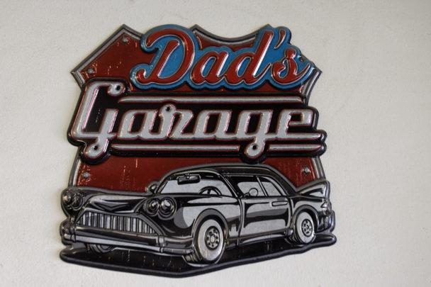 """En liten skylt med en stiliserad bil och texten: """"Dad's Garage"""""""