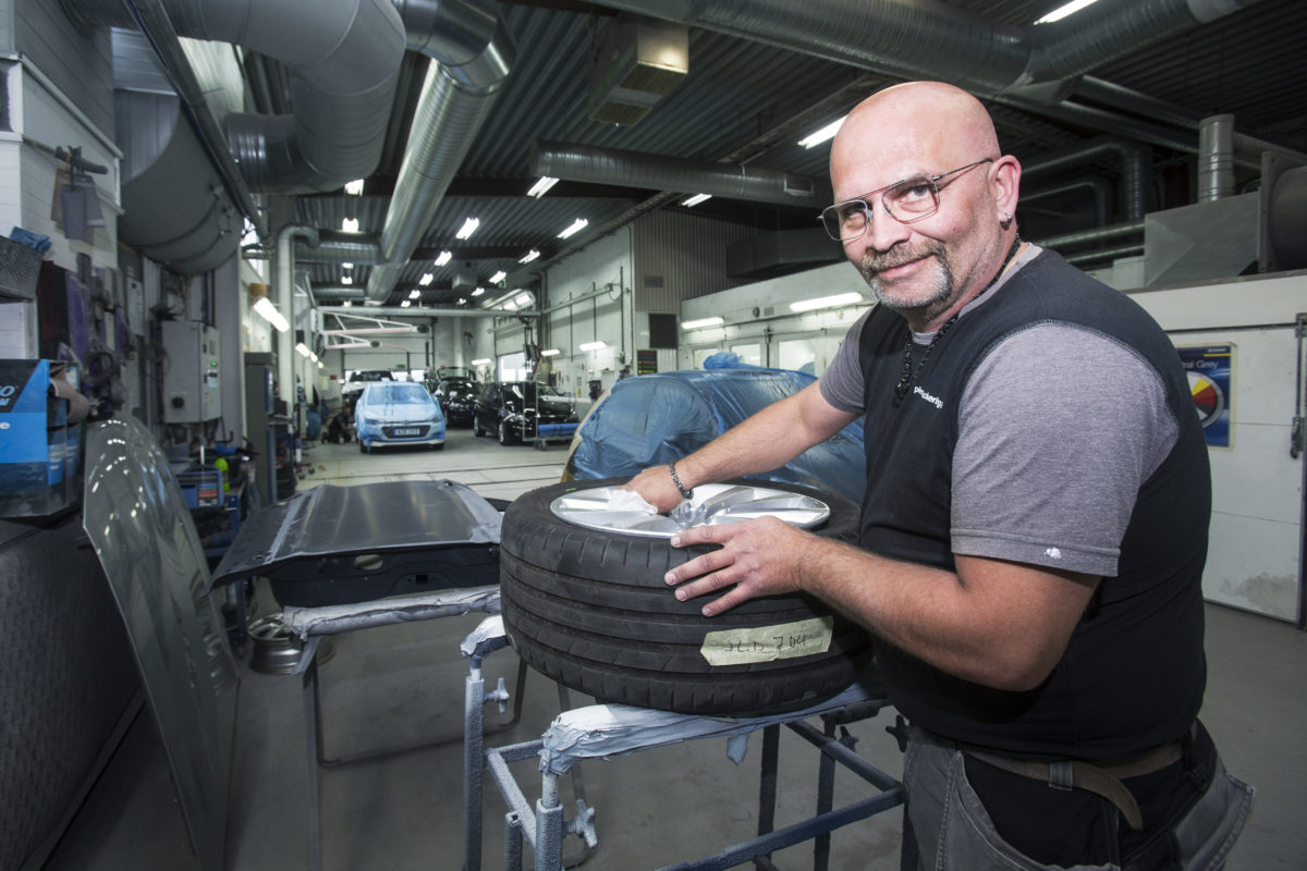 Karl-Gustav Klase ler mot kameran medan han rabatter invid ett bildäck i verkstaden