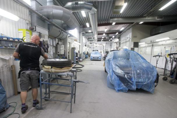 Karl-Gustav Klase arbetar i verkstaden, med en övertäckt bil i bakgrunden