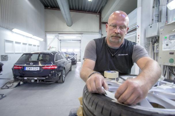 Karl-Gustav Klase arbetar vid ett bildäck i verkstaden, med en bil i bakgrunden