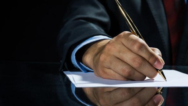 Handen på en person i kostym som skriver på ett papper med en fin penna