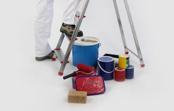 En person är på väg upp på en stege, nedanför vilken det står en samling färgburkar och verktyg
