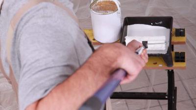 En person som målar med en lång roller