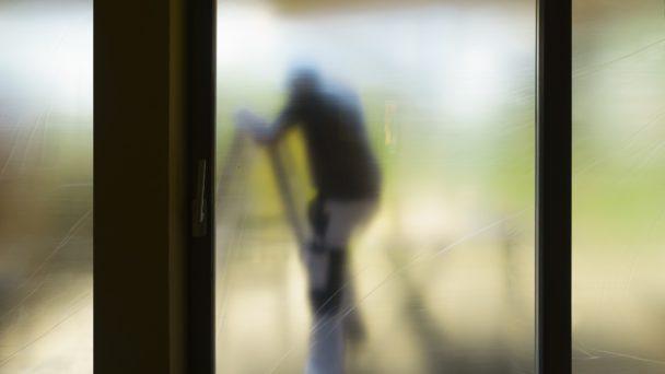 Silhuetten av en målare som klättrar på en stege, sedd genom en grumlig yta.