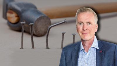 En hammare och en rad sneda spikar, med ett porträtt av Mikael Johansson monterat över.