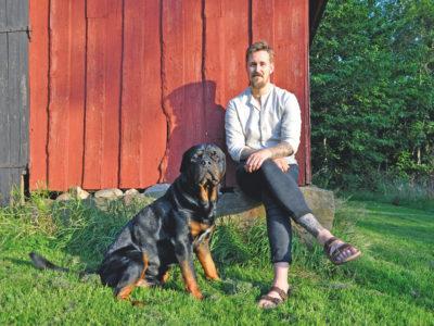 Jakob Nilsson sitter vid en röd husknut med en hund bredvid sig.