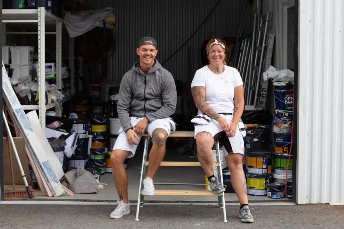 Robin Törnborg och Malin Melin på en stegpall framför ett utrustningsförråd