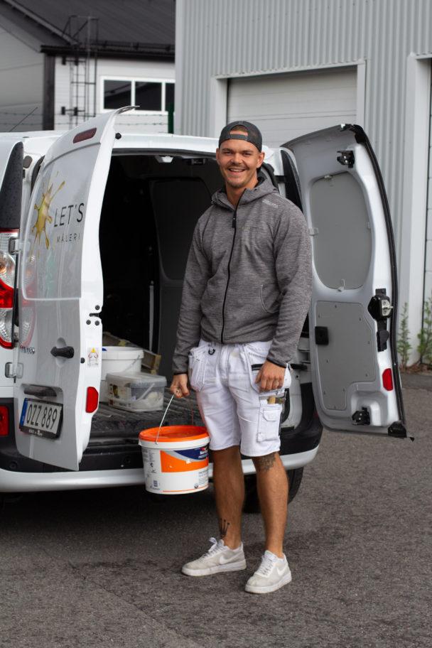 Robin Törnborg hållandes en färgburk vid firmabilen
