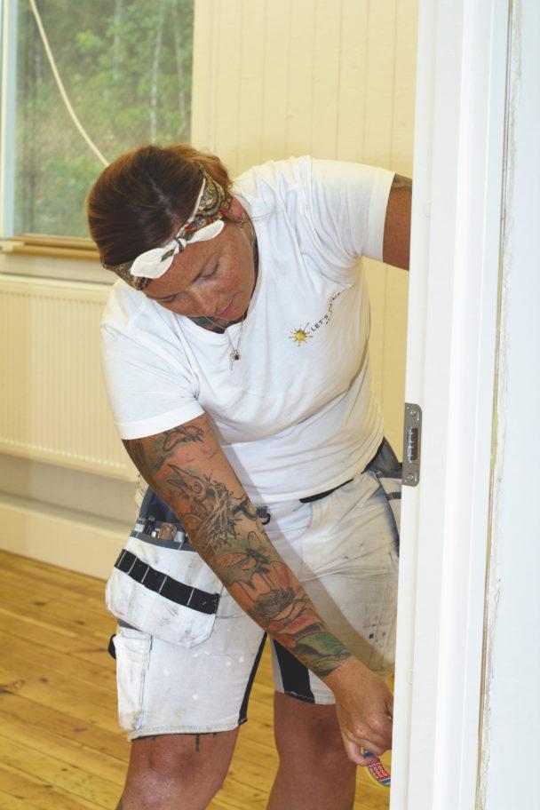Malin Melin målar en dörrkarm
