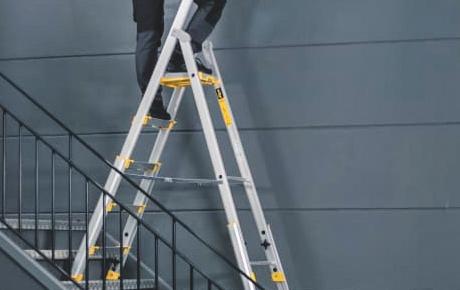 En person arbetar på en stege som står i en trappa