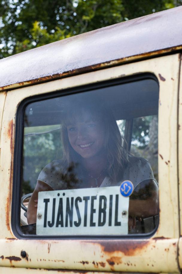 """Malin Gullbrandsson tittar ut genom fönstret på en av sina folkvagnar. """"Tjänstebil"""" står det på en skylt i fönstret."""