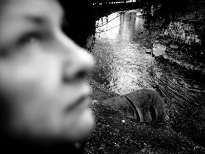 Svartvit bild på en person i profil i regn