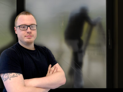 Stefan Lövstrand monterad framför en målare på en stege bakom ett suddigtskynke