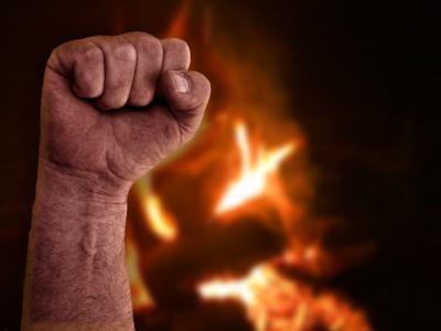 En knuten näve höjd framför en eld