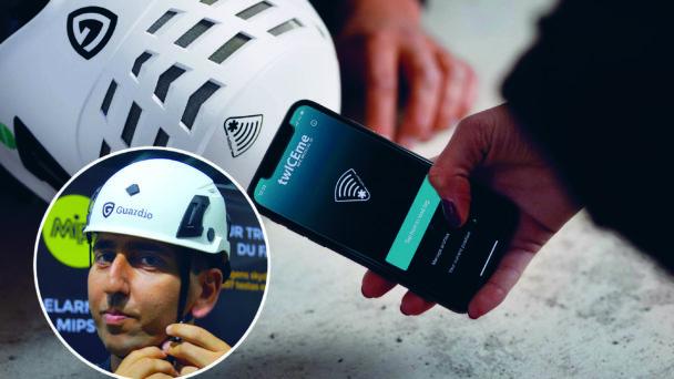 En hand håller i en mobiltelefon med appen från texten, framför en liggande person med hjälmen på. Ett foto på Nawar Toma med hjälmen på sig är monterat i hörnet