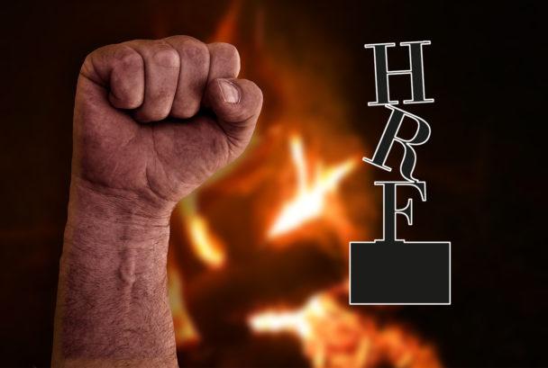 En knuten näve framför eld, med HRF:s logga monterat över