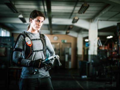 En person med exoskelettet på sig, hållandes ett verktyg