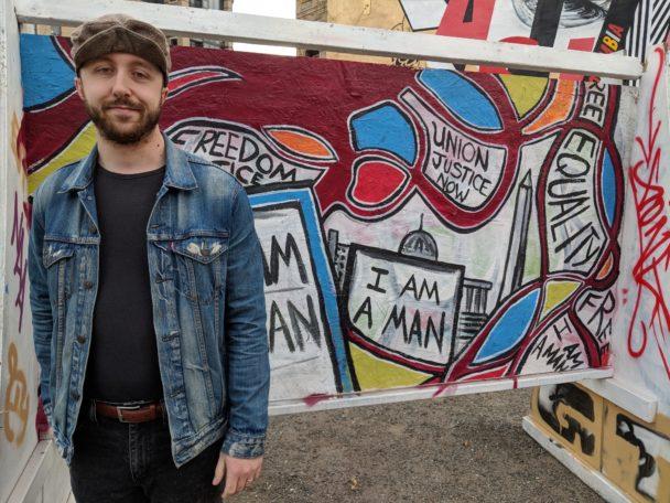 Ryan Kekeris framför en vägg med graffiti