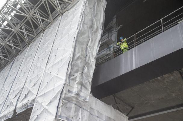 Bild nedifrån, på en person som står uppe på bron