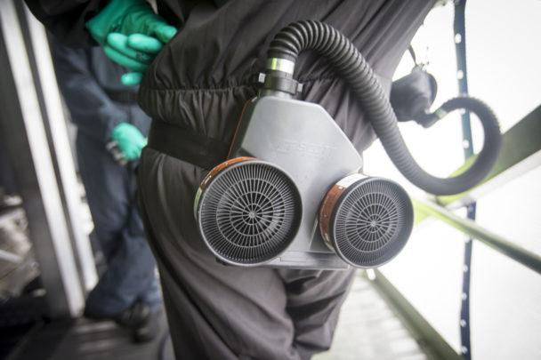 Benen på en person med fläkt och friluftsmask hängande i bältet