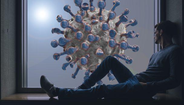 En person sitter i ett fönster och tittar ut på En illustration av det nya coronaviruset