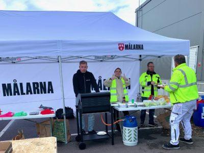 Jonathan Andersson, Johanna Lillbacka och Stefan Lövstrand vid ett grillbord i ett tält