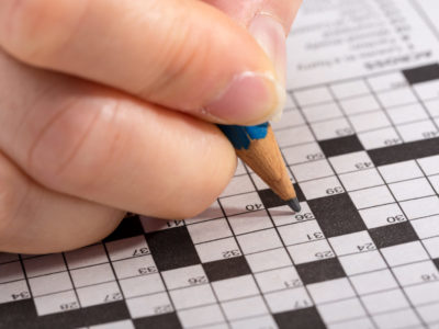 En hand med en penna som löser korsord
