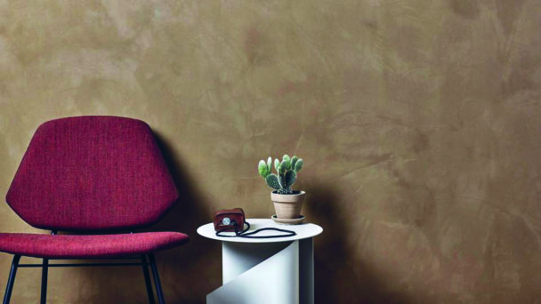 Ett rum med en vägg målad med spackelfärg. Framför väggen står en stol och ett bord med en växt på.