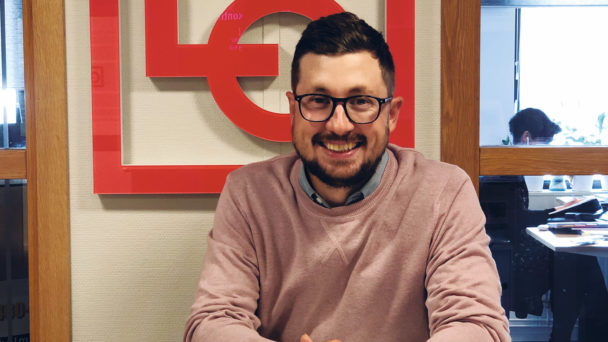 Dan Mattsson, leende vid ett bord framför LO:s logga