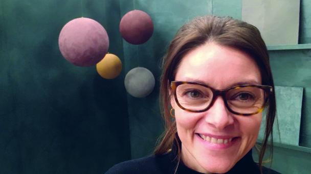 Therese Johansen framför en vägg målad med den grå färgen. Färgglada bollar hänger från taket bakom henne.