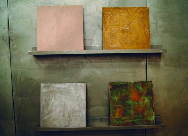 Fyra exempelplattor i olika färger, stående på väggkonsoler