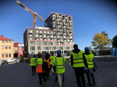 En grupp personer i gula reflexjackor på väg mot ett bygge