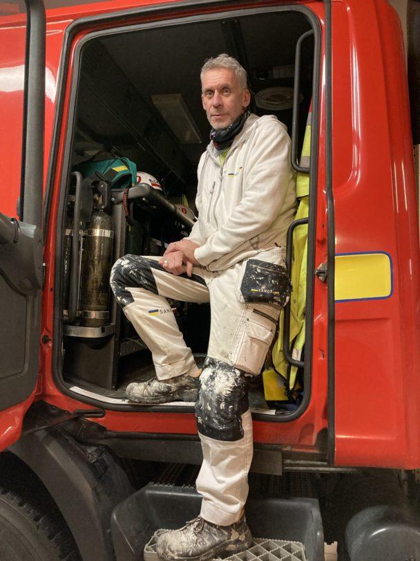 Roland Berg innanför sidodörren på en brandbil